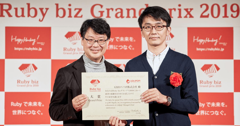 授賞式の会場で審査委員長のまつもとゆきひろ氏とGMOペパボ株式会社のプリンシパルエンジニアの小山健一郎が大賞の賞状を持って並んでいる写真